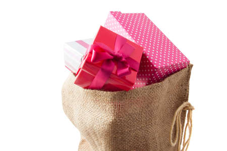 Jute bag filled with gifts on a white background photo
