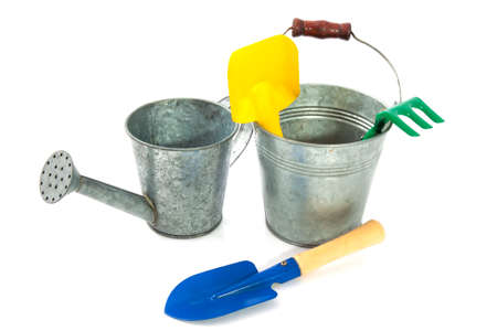 Zinc bucket with watering can shovel and rake isolated over white photo