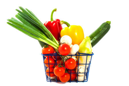 Shopping basket filled with vegetables isolated over white photo