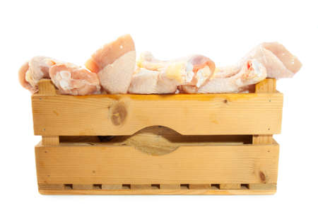 Wooden crate filled with chicken legs isolated over white photo