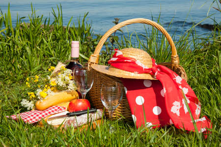 Picnic basket in the grass with tasty food and wine photo
