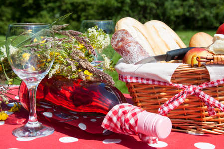 picknick: Picnic basket in the grass with tasty food and wine
