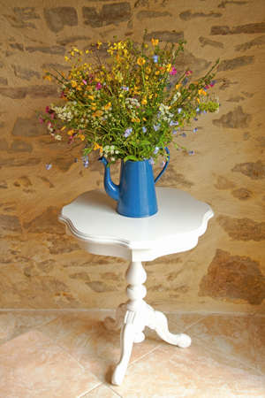 Bouquet field flowers in blue watering can on a table  in front of a stone background photo