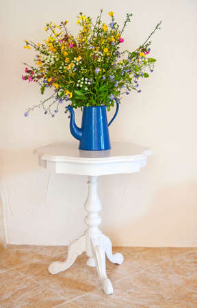 Field flowers in blue vase on white table in front of white wall photo