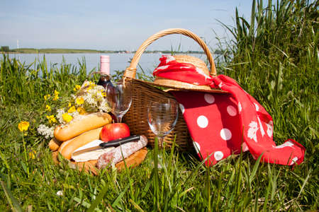 Picnic  in the grass with tasty food and wine photo