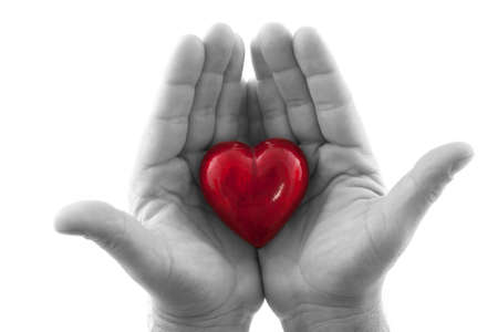 kindness: Hands holding a heart on white background