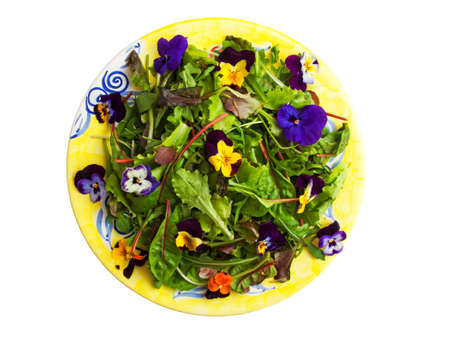 Mixed salad with flowers on a yellow plate isolated over white