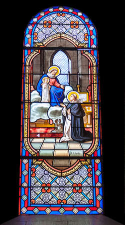 Colorful stained glass with mother mary and child jesus with a preacher