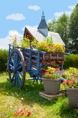 Blue covered wagon surrounded by flowers in france