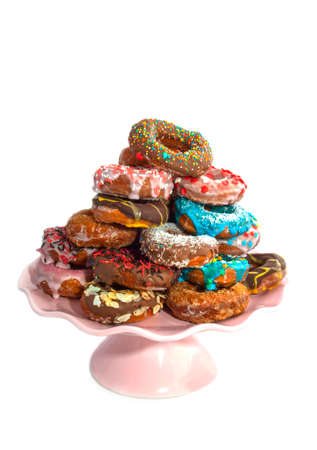 phillip rubino: Decorated colorfull donuts with sweets on a pile isolated over white