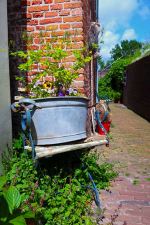 Rustic old dutch street with flower bucket
