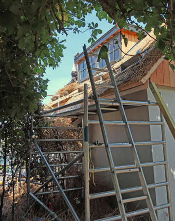 Straw roof under construction with a ladder Stock fotó - 134748591