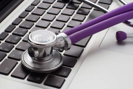 stethoscope lying on laptop keyboard photo