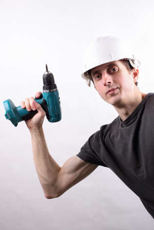 journeyman technician: working professional in the helmet with a drill on a white background