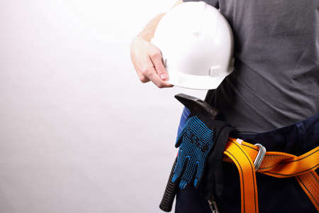 working professional with helmet in hand on white background