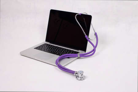 Medical stethoscope and laptop on a white background photo