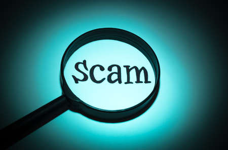 scamming: Concept search loupe magnifier scam button Stock Photo
