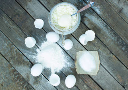 preservatives: Eggs, flour, cottage cheese, sour cream, sugar and spoon on a wooden table top. Selective Focus Stock Photo