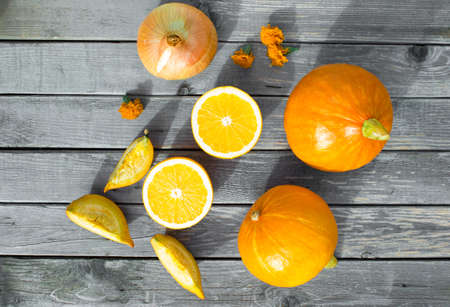 quartered: The concept of the collection of sliced pumpkin pieces to share, oranges and bow. Autumn sliced pumpkin pieces to share, oranges and bow of on a wooden table. Selective Focus Stock Photo