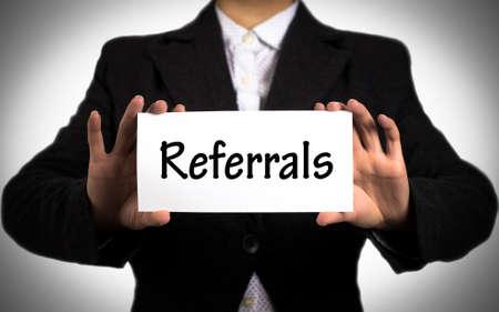 referidos: Empresaria en una chaqueta negro y una camisa blanca muestra una tarjeta con las referencias de inscripci�n. Chica sobre un fondo blanco. enfoque selectivo. Foto de archivo
