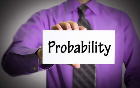 probability: Businessman in blue shirt and gray tie shows a card with the inscription probability. Man on a gray background. Selective focus. Stock Photo