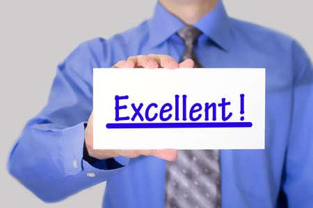 ottimo: Uomo d'affari in camicia blu e cravatta grigia mostra una scheda con l'eccellente iscrizione. L'uomo su uno sfondo grigio. messa a fuoco selettiva.