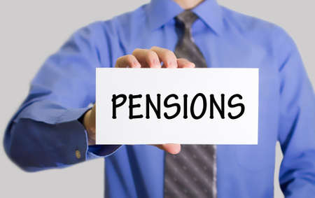 subsidize: Businessman in blue shirt and gray tie shows a card with the inscription pensions. Man on a gray background. Selective focus.