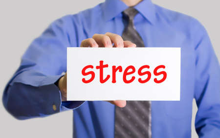stressing: Businessman in blue shirt and gray tie shows a card with the inscription stress. Man on a gray background. Selective focus.