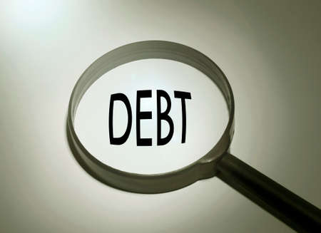 managing money: Magnifying glass with the word debt. Searching debt