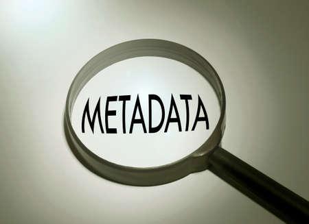 metadata: Magnifying glass with the word metadata. Searching metadata Stock Photo