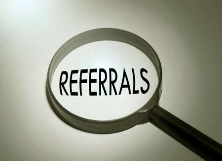 referidos: Magnifying glass with the word referrals. Searching referrals