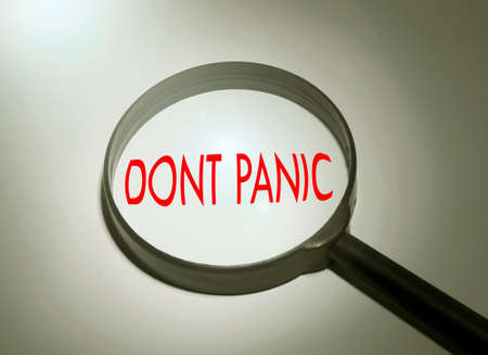 panic: Magnifying glass with the word dont panic. Searching dont panic Stock Photo
