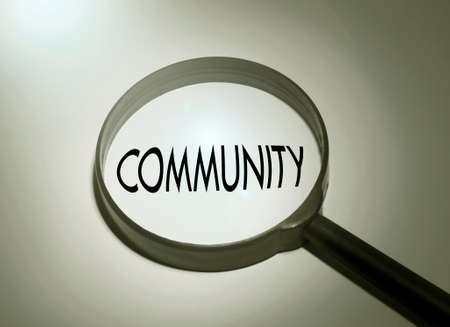 altogether: Magnifying glass with the word community. Searching community Stock Photo