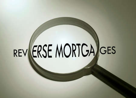 reverse: Magnifying glass with the word reverse mortgages. Searching reverse mortgages