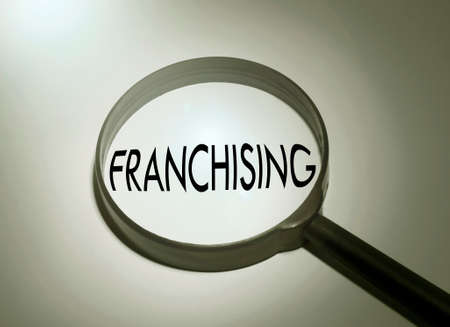 franchising: Magnifying glass with the word franchising. Searching franchising Stock Photo