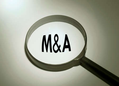 mergers: Magnifying glass with the word M&A (mergers and acquisition)
