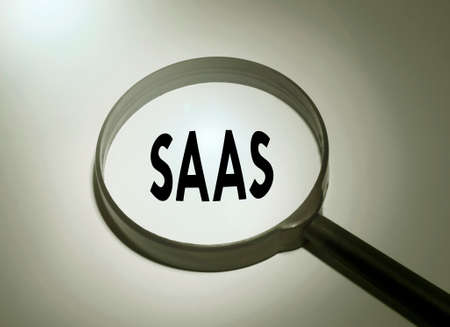 Saas Fee: Magnifying glass with the word SAAS (software as a service) Stock Photo