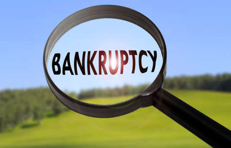 Magnifying glass with the word bankruptcy on blurred nature background. Searching bankruptcy concept Stock Photo