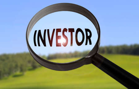 Magnifying glass with the word investor on blurred nature background. Searching investor concept