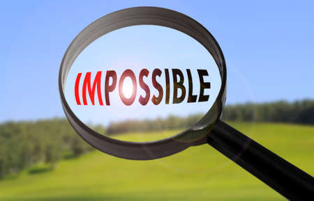 Magnifying glass with the word impossible on blurred nature background. Searching impossible concept