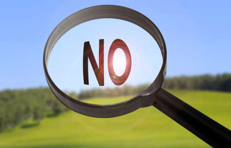 disclaim: Magnifying glass with the word no on blurred nature background. Searching no concept Stock Photo