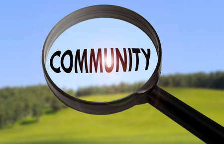 Magnifying glass with the word community on blurred nature background. Searching community concept