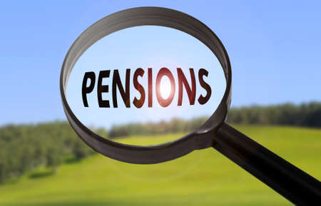 pensions: Magnifying glass with the word pensions on blurred nature background. Searching pensions concept