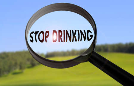 Magnifying glass with the word stop drinking on blurred nature background. Searching stop drinking concept
