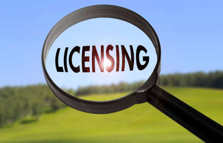 licensing: Magnifying glass with the word licensing on blurred nature background. Searching licensing concept