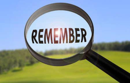 recordar: Lupa con la palabra recordar en el fondo la naturaleza borrosa. Busca recordar concepto