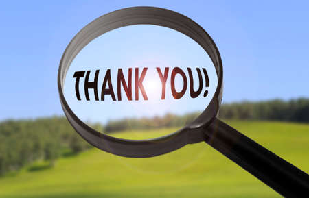 Magnifying glass with the word thank you on blurred nature background. Searching thank you concept Stock Photo