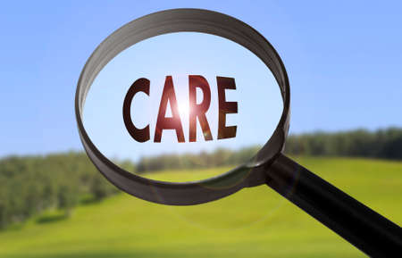 Magnifying glass with the word care on blurred nature background. Searching care concept Stock Photo