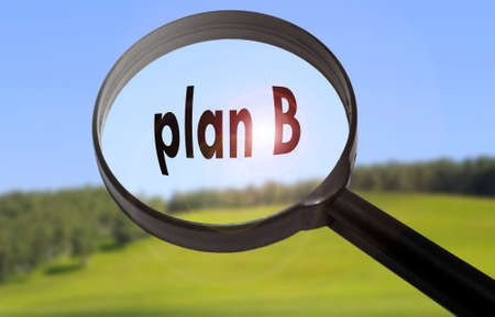 Magnifying glass with the word plan b on blurred nature background. Searching plan b concept Stock Photo