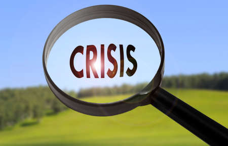 Magnifying glass with the word crisis on blurred nature background. Searching crisis concept